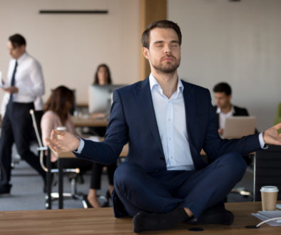 Businessman in suit sitting on table and meditating in office